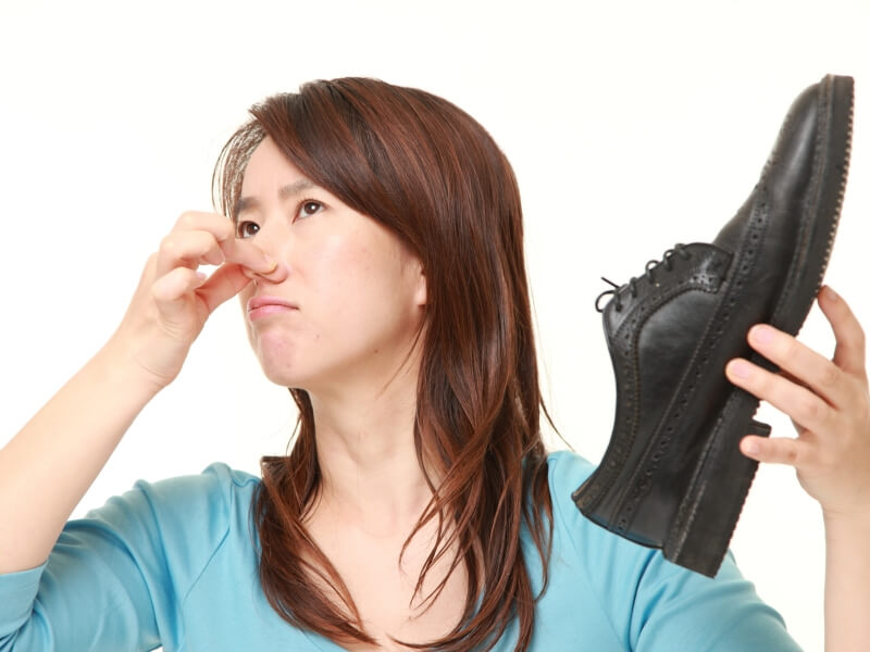 靴の臭いに鼻をつまむ女性
