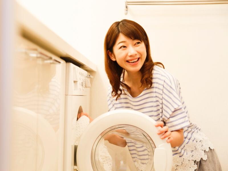 洗濯機の扉を開ける女性