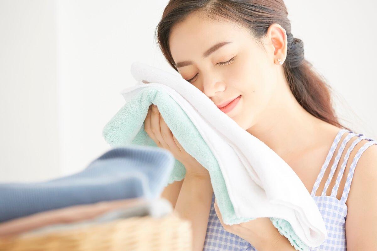 タオルを頬に寄せる女性