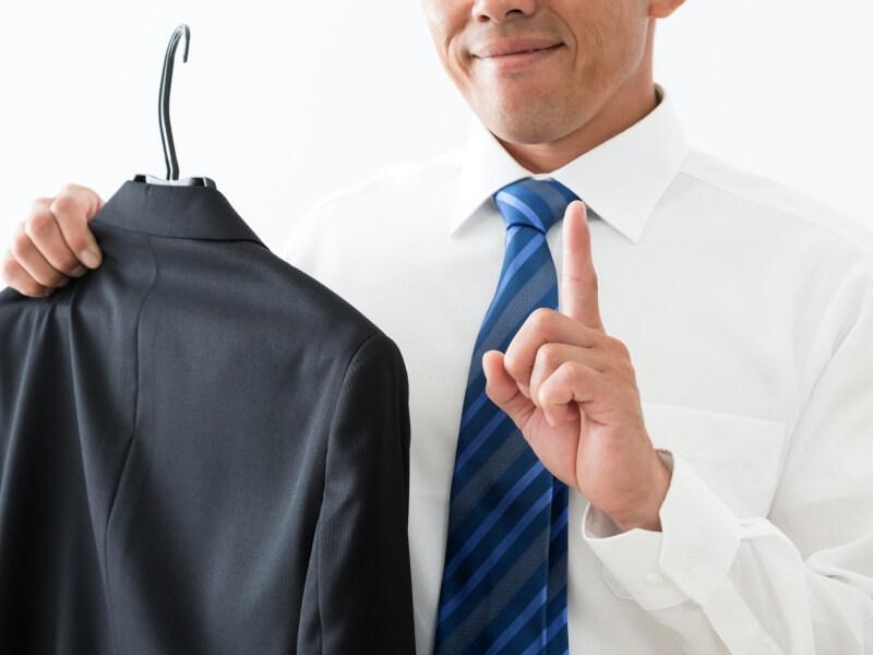 スーツを持つ男性