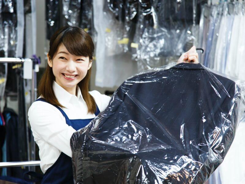 ジャケットを持つクリーニング店の女性