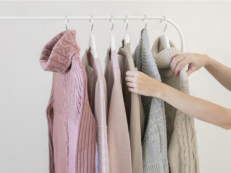 ハンガーにかけられたセーターを選んでいる
