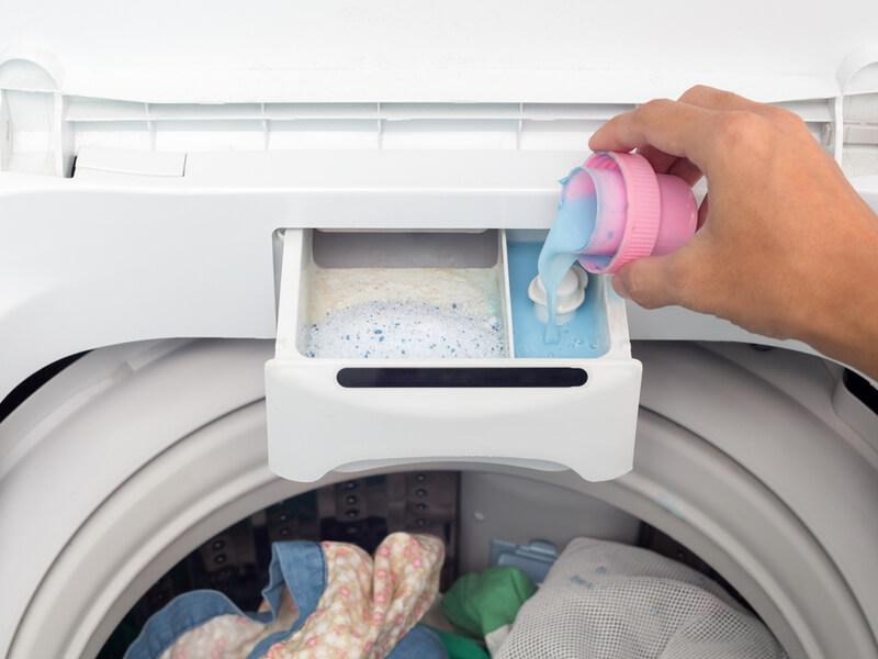 洗濯機に柔軟剤を入れているところ