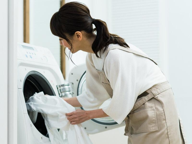 洗濯機に洗濯物を入れている女性