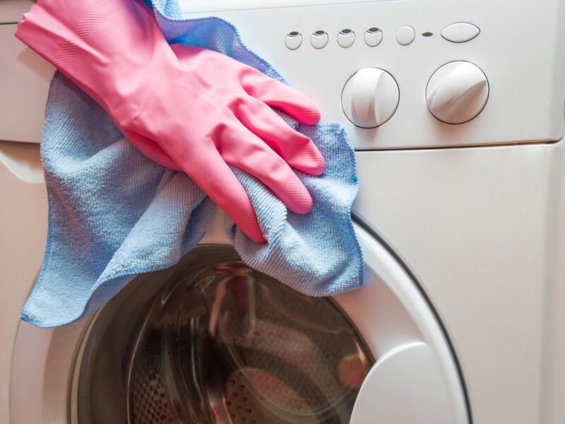 洗濯機の外側を掃除している