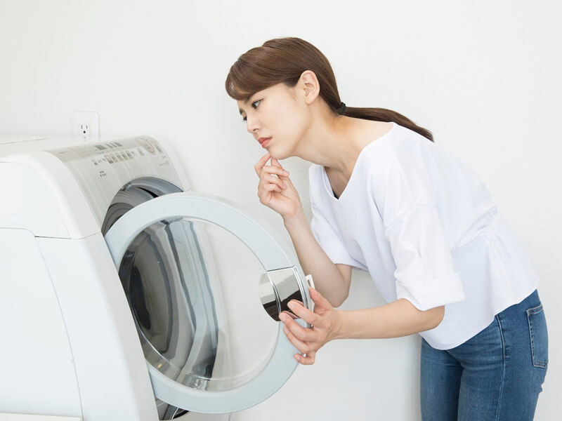 洗濯機をあけて悩んでいる女性