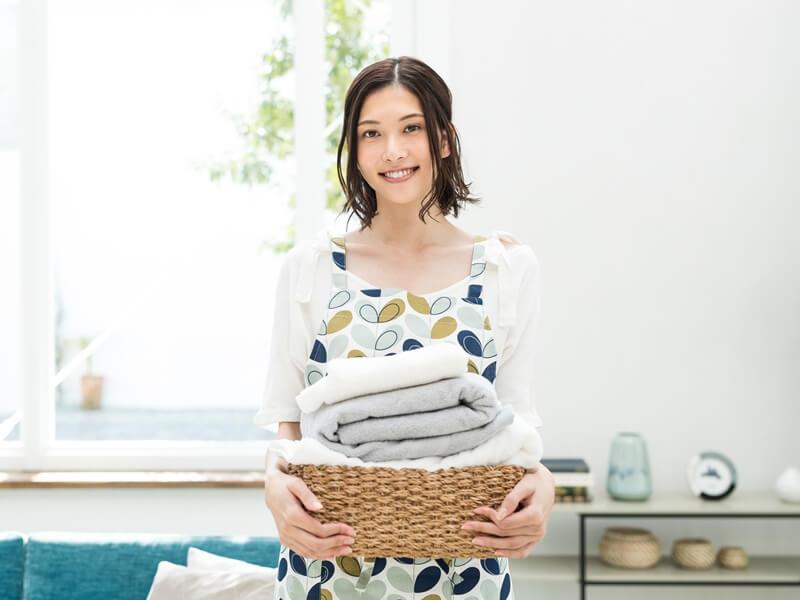 洗濯を持って笑顔の女性