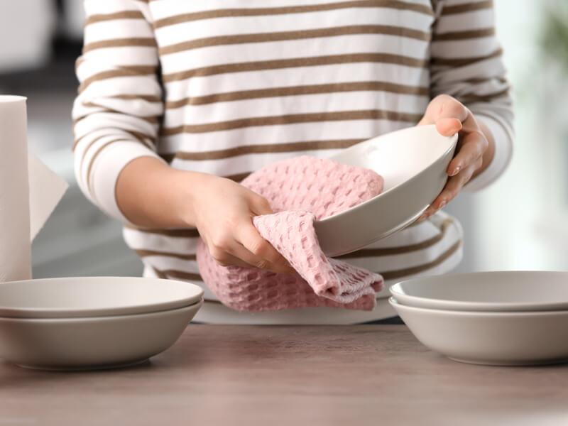 キッチンタオルで食器を拭いている女性