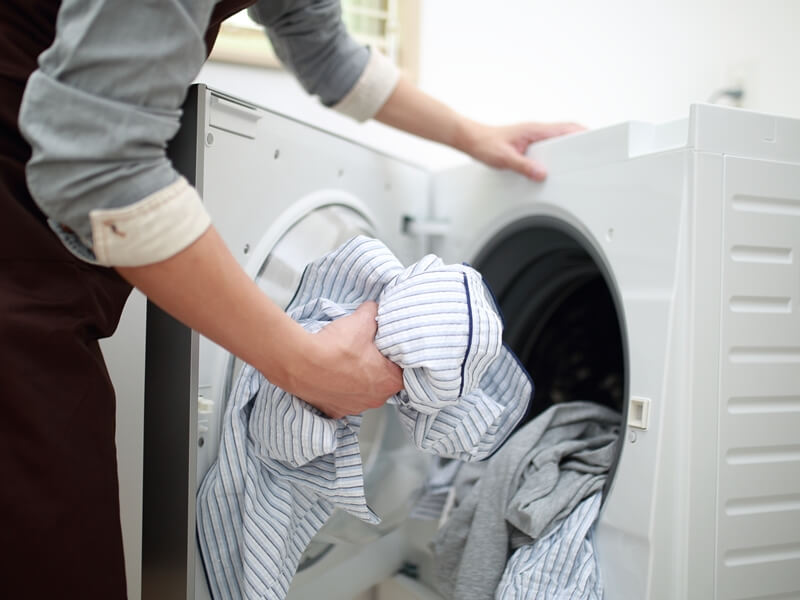 乾燥機に洗濯物を入れてい