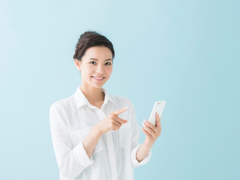 携帯を利用して口コミを見ている女性