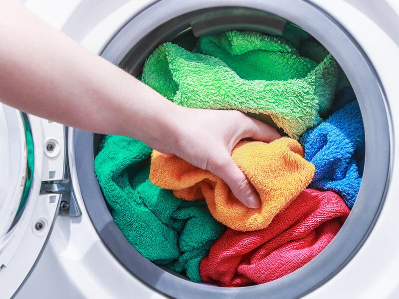 洗濯機にタオルを詰め込んでいる