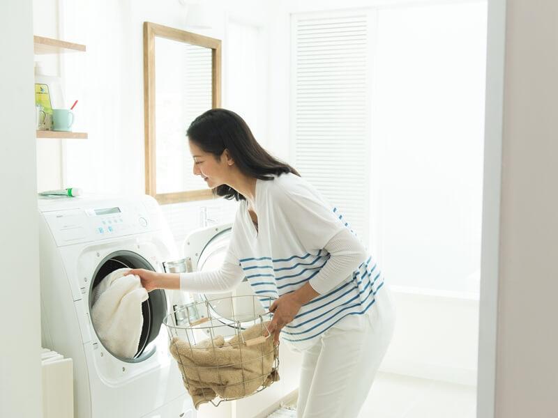 洗濯機に洗濯物を入れている