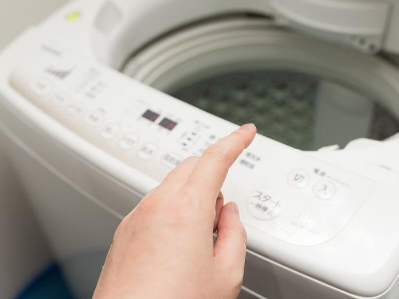 洗濯機のスタートボタンを押すところ