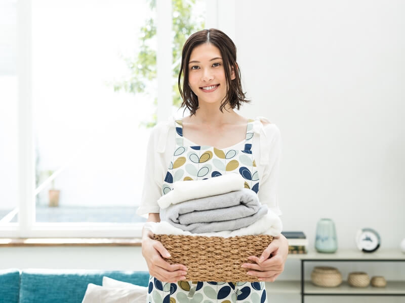 洗濯物を手にして笑顔の女性