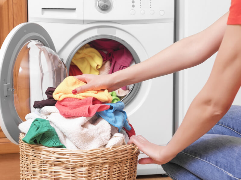 洗濯物を洗濯機に詰めている